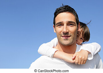 Young boy riding piggy-back on his father's back