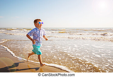 young boy run on the shore