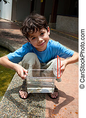 Young boy showing off his little container of fish he just caught.