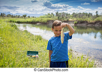 Young boy showing the fish he caught.
