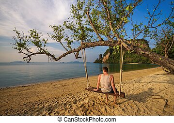 Young boy sits on a swing on Ko Hong island in Thailand