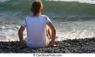 young boy sits on pebble beach and throws stone at sea, back...