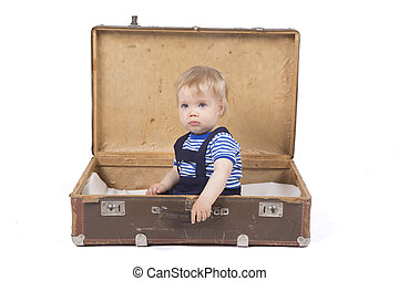 Young boy sitting in a suitcase