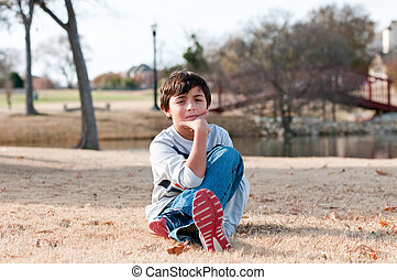 Young boy sitting in grass looking serious outdoors