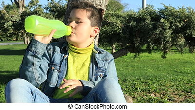 Young boy sitting on a lawn and drinking water