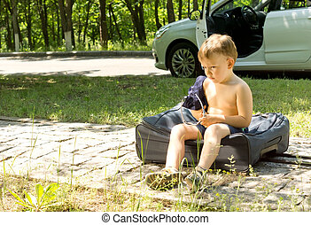 Young boy sitting on a travel bag on the roadside