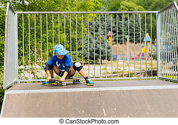 Young Boy Sitting on Skateboard at Top of Ramp