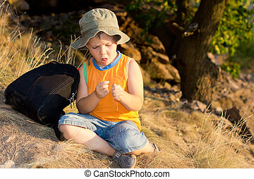 Young boy sitting on the ground with a rucksack