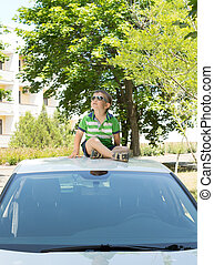 Young boy sitting on the top of a car looking up