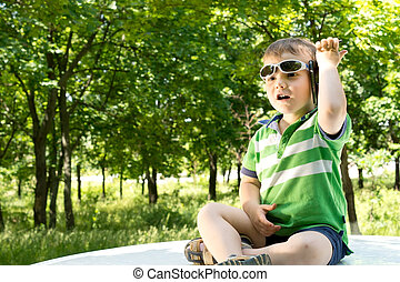 Young boy sitting on the top of a car with a phone