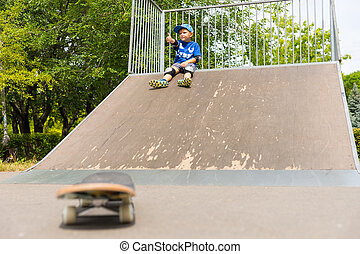 Young Boy Sitting on Top of Ramp in Skate Park