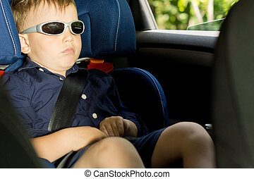 Young boy sleeping in the child car-seat
