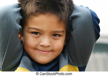 Close up portrait of a young boy child smiling with arms up behind his head.