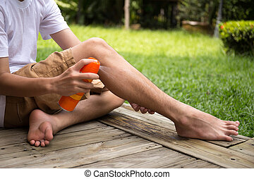 Young boy spraying insect repellents on his leg  with spray bottle
