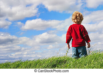 Young boy standing at the top of a hill