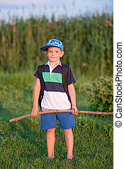 Young Boy Standing in Field Holding Large Stick