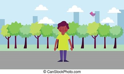 young boy standing in the street with trees birds flying in the city