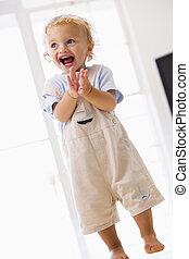 Young boy standing indoors applauding and smiling