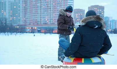 Young boy starts pulling sled with other boy in winter