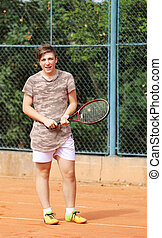 Young boy stay on tennis court