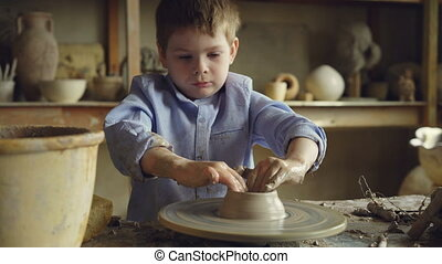 Young boy student of pottery class is molding clay on potter's wheel, learning traditional craft. Serious child is concentrated on work, getting new experience.