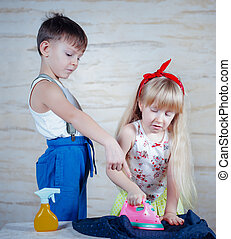 Young boy supervising a young girl ironing