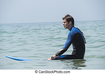 Young boy surfing in the sea, waiting waves