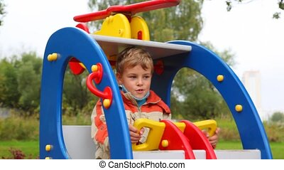 young boy swinging in toy helicopter in children playground