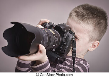 Young boy taking pictures