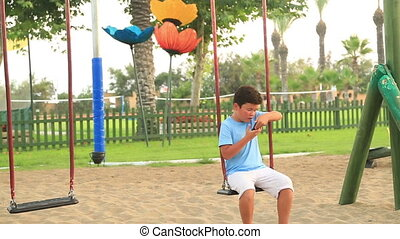Young boy talking on the phone in the playground - Young boy...