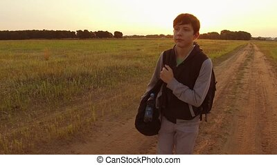 Young boy teenager man walking on a countryside road travel journey