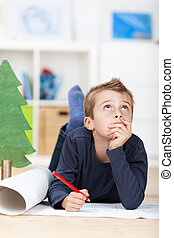 Young boy thinking about wishes for christmas