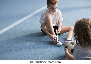 Young boy tying sport shoes