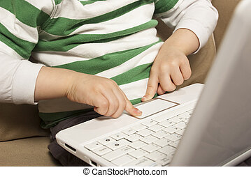 Young boy uses touchpad on Net Book laptop