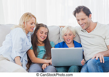 Young boy using a laptop with his family