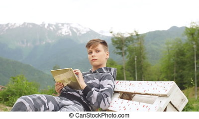 Young boy using digital tablet pc outdoor
