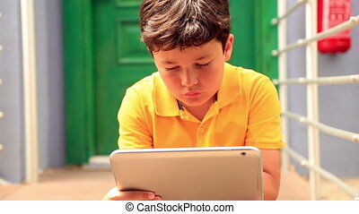 Young boy sitting on a stairs, in front of the door and using digital tablet outdoor