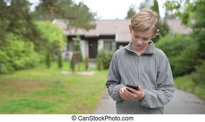 Young Boy Using Phone And Taking Selfie At Home Outdoors -...