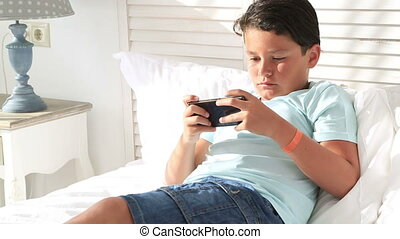 Young boy using smartphone at home