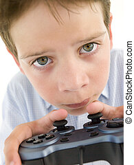 Young boy using videogame controller and concentrating