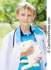 Young boy veterinary and little rabbit happy smiling & looking at camera on summer green outdoors background