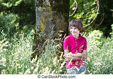 Young boy waliing in a park on a sunny day