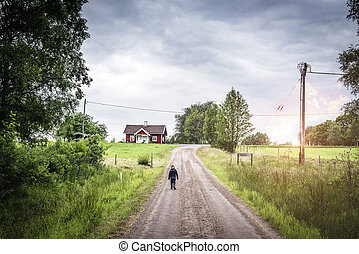 Young boy walking down a road in rural environment