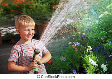 Young boy watering flowers