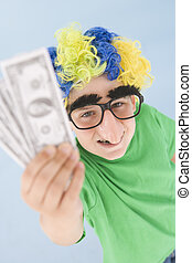 Young boy wearing clown wig and fake nose holding money