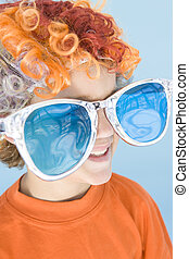 Young boy wearing clown wig and sunglasses smiling