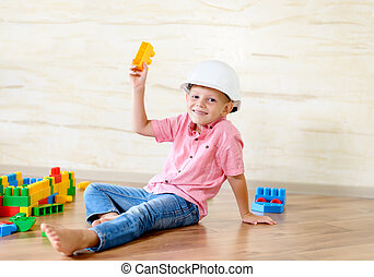 Young boy wearing hardhat playing indoors