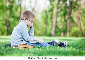 young boy with a book and laptop computer
