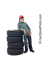 Young boy with a set of car tires
