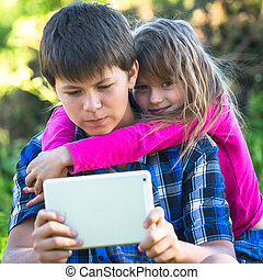 Young boy with a tablet PC and his little sister looking into the camera, outdoors.
